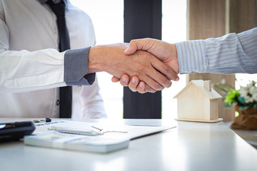 Both businessmen shake hand to congratulate them on their successful signing of a contract with a home insurance agent, housing purchase and insurance Concept.