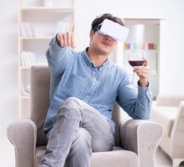 Young man drinking wine at home