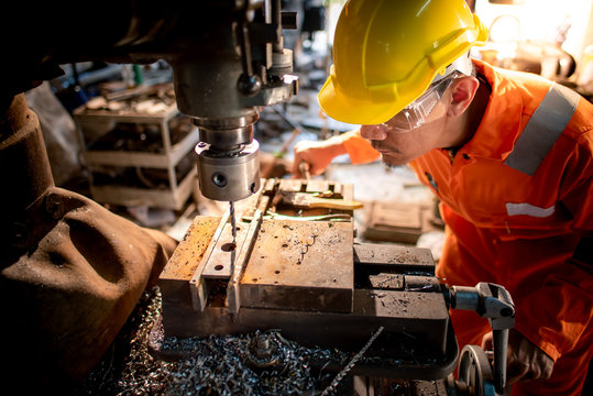 Workers in the shop wear orange work clothes and wear glasses to prevent metal chips from penetrating. Stand beside the drilling rig and use metal drills in industrial plants
