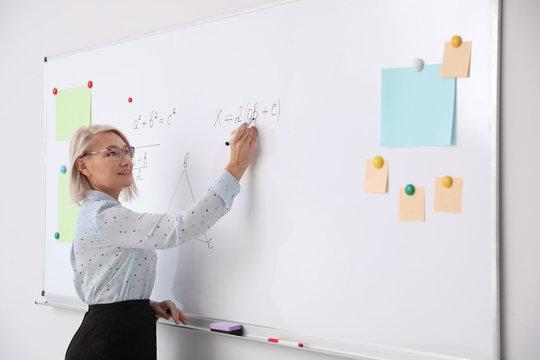 Mature teacher writing on whiteboard in modern classroom