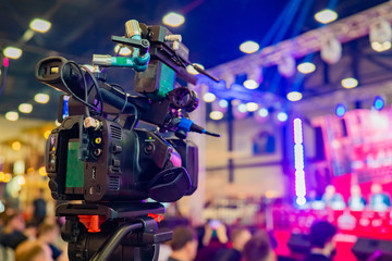 The professional camera is aimed at the scene. Professional camera on a tripod. Camera for video shooting near the audience. Concept - organization of video filming. Professional video shooting