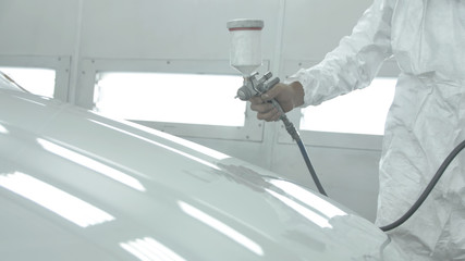 Process of painting a white car in a spray booth. Man using a spray gun Wall mural