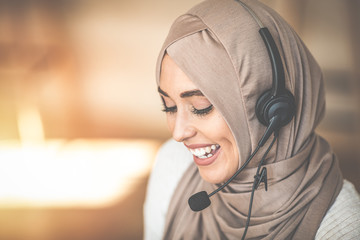 Woman wearing headscarf and headset talking while working in a call centre office, smiling, close-up. Close up beautiful muslim woman call center agent wear headset device and smiling