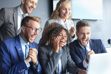 Happy business people laugh near laptop in the office. Successful team coworkers joke and have fun together at work.