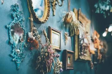 ドライフラワーやフォトフレーム 、ミラーで飾られた青い壁