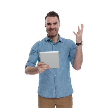Angry casual man holding tablet and gesturing