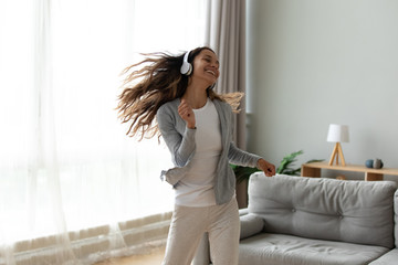 Overjoyed millennial girl wearing headphones have fun moving listening to music relax in living...