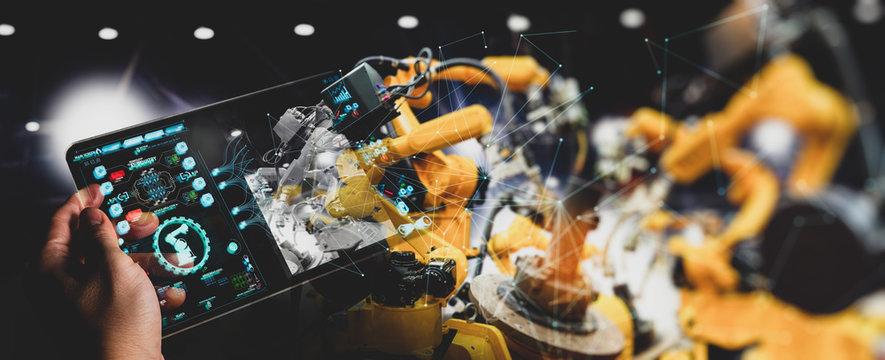 Engineer hand using digital tablet and checking welding robotics automatic arms machine. Augmented reality in intelligent factory  industrial with monitoring system software.