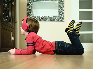 Child with headphones on the floor playing console