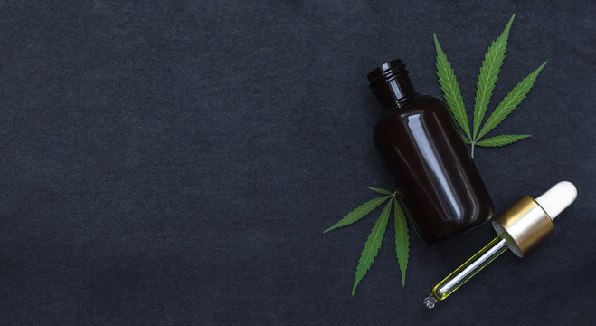 CBD oil or tincture make with cannabis on black background with copy space left. Medical marijuana product.