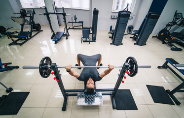 Bodybuilder trainer man doing bench press workout in gym. Photo from the top. Strong abs. Health life sport concept.