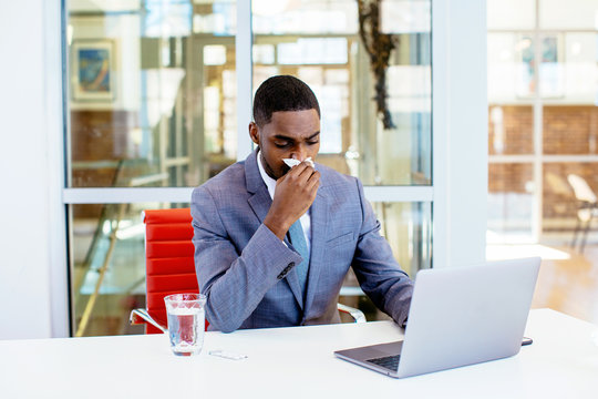 Portrait of a sick young man in business suit having a cold,  blowing his nose while sitting behind desk at work with computer