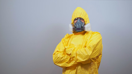 A man in yellow Hazmat suits and a respirator stands on a gray background with his arms crossed over his chest. Wall mural