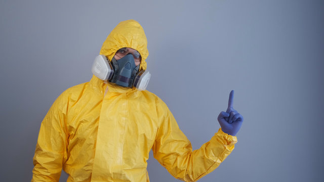 A man in a yellow chemical protection suit on a gray background raises his index finger up. Copy space
