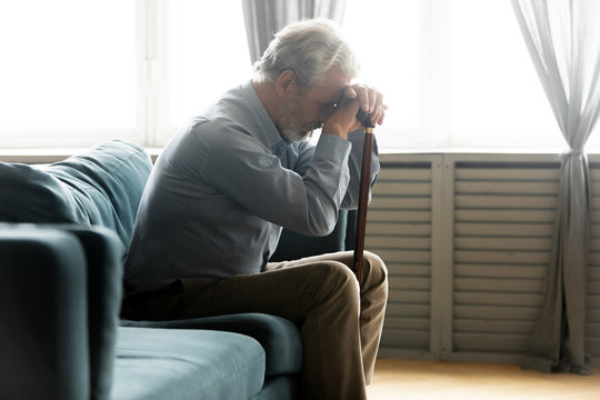 Depressed unhappy old man sit on couch at home hold wooden stick feel abandoned lonely, sad mature 60s male with walking cane suffer from loneliness or depression, elderly solitude concept