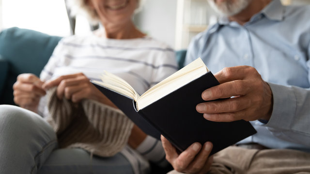 Close up of happy retired elderly couple spouses sit relax on couch enjoy leisure weekend at home together, smiling mature 60s husband reading book in living room, middle-aged 50s wife do knitting
