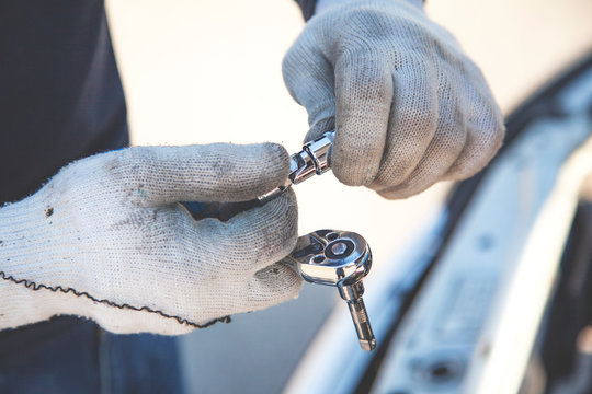 Mechanic male worker using with ratchet socket wrench