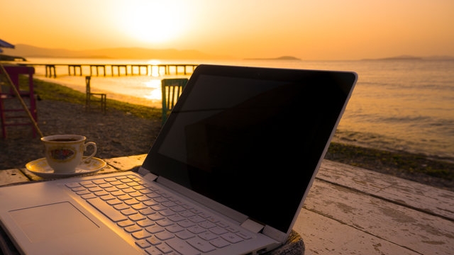 Freelance working with laptop on wooden table on beach at sunset. Woman sitting on chair and using computer near blue sea shore at sunny day. Digital nomadism towards yellow sky & horizon
