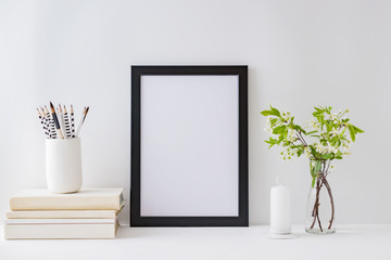 Home interior with decor elements. Mockup with a black frame, spring flowers in a vase on a light background