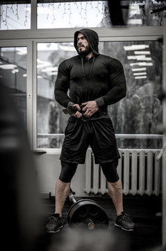mental and physical growth concept of hard workout training in gym by strong young athlete caucasian man wearing hoodie and powerlifting belt near barbell