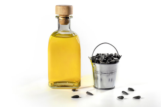 A bottle of sunflower oil with a bucket of seeds on a white background.