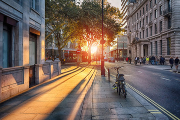 Looking towards the setting sun on Pall Mall East with bus, taxi, bicycle and people with blurred faces Fotomurales