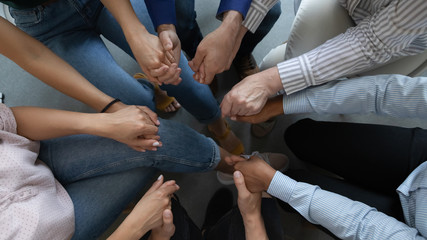 Close up top view of diverse multiracial businesspeople sit in circle hold hands showing support...
