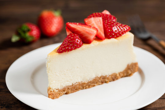 Cheesecake with strawberries on plate, wooden table background
