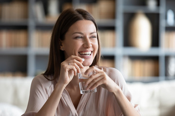 Head shot smiling young woman holding pill and glass of fresh pure water. Healthy millennial lady taking antioxidant medicine vitamins, beauty supplements for hair skin nails, healthcare concept.