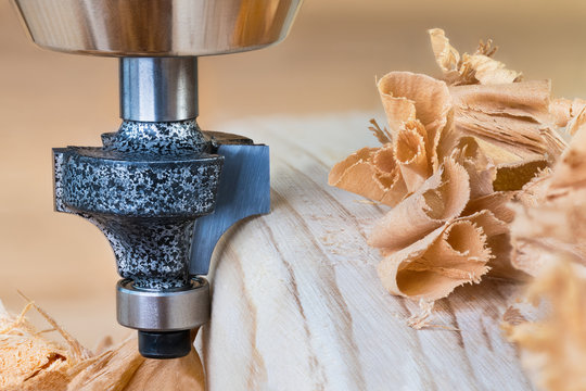 Shaping copying shank router bit clamped in chuck of a working machine tool. Sharp steel woodworking milling cutter with bearing forming a round edge on wood plank. Pile of twisted shavings. Joinery.