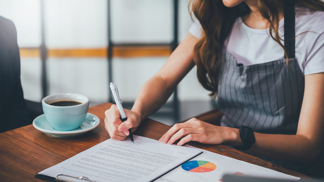 Asian women coffee shop owner is signing the contract. Start a new business On the table with a coffee cup and data sheets paper.Small business finance concepts.Vintage tone.