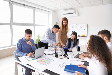 Architect teaching young people in office