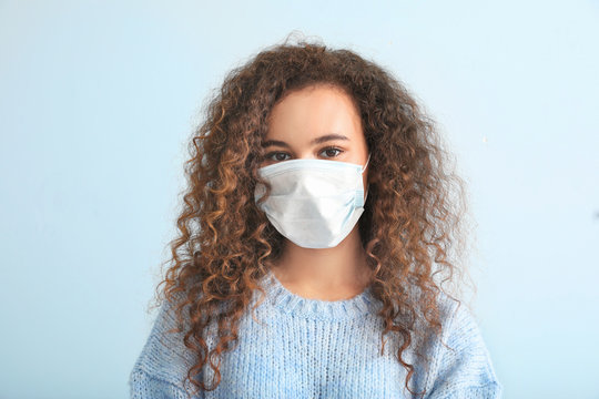Young woman with protective mask on light background. Concept of epidemic