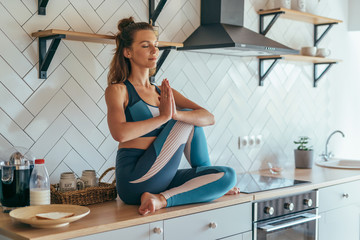 Fit concentrated caucasian woman sitting on talbe in kitchen and meditating