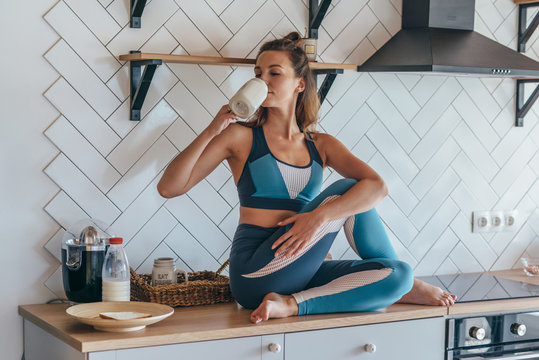 Athletic woman having breakfast in the kitchen, girl sitting on table and drinking