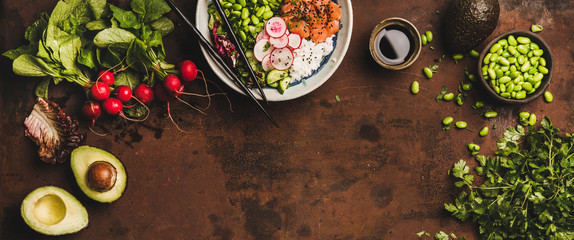 Flat-lay of salmon poke bowl or sushi bowl with vegetables, greens, sushi rice, soy sauce and ingredients over dark rusty table background, top view, copy space, wide composition