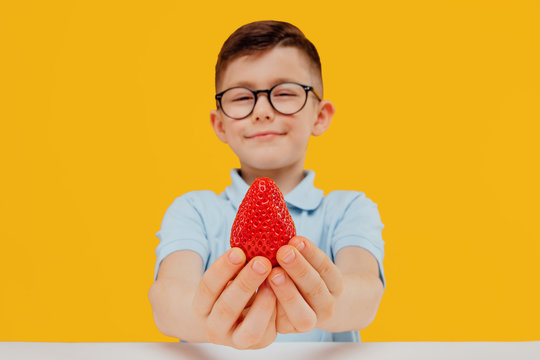 little boy in glasses holds a strawberry in hand. isolated on yellow background looks at camera
