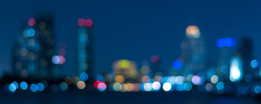 Banner cover of blurred bokeh cityscape at twilight time, city background, aerial view angle from rooftop ob building, defocused city in downtown,graphic design for web online or book horizontal cover