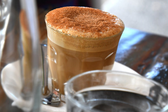 Frothy top coffee in glass at cafe table.