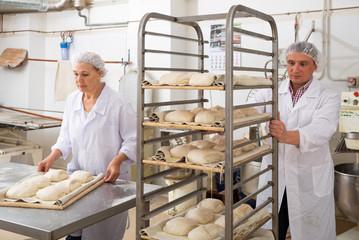 Keuken foto achterwand Bakkerij Male and female baker working together in bakery shop