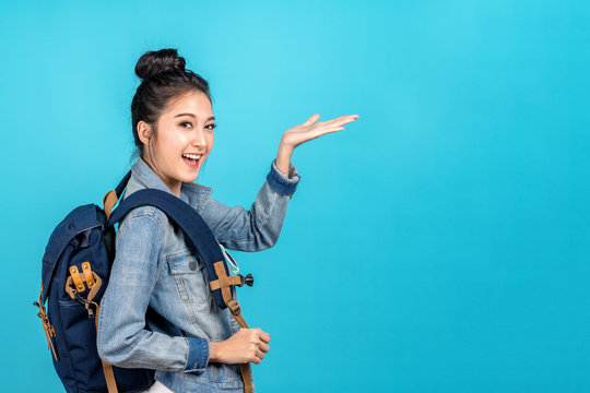 Happy asian woman travel backpacker standing hand open to copyspace on blue background. Cute asia girl smiling wearing casual jeans shirt and finger pointing to aside for present promotions.