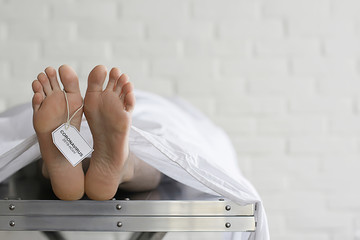 concept imitation morgue, coronavirus victim killed by 2019-ncov, legs of a corpse on a table, man...