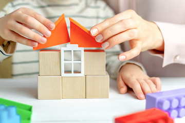 Mom and child build a house of wooden cubes and blocks constructor. Close up of hands holding roof elements. Playing parents and children at home. Credit, real estate and mortgage financial concept.