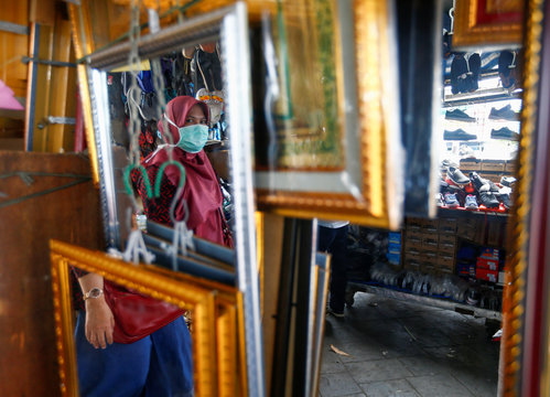 Woman wearing a protective face mask walks past a mirror, after Indonesia confirmed new cases of coronavirus disease (COVID-19), in Jakarta