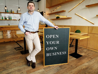 Businessman holds Open your own business sign. Wall mural