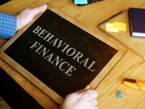 Man holds Behavioral Finance sign on the blackboard.