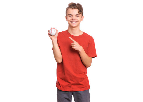 Portrait of happy teen boy holding baseball ball, isolated white background. Smiling teenager showing small ball. Happy child. Sport, exercise, training concept.