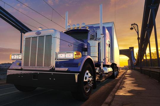 American Peterbilt truck with a semitrailer driving across the bridge at sunrise