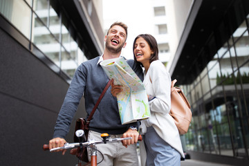 Holidays, dating and tourism concept. Smiling couple in love with map in the city Wall mural