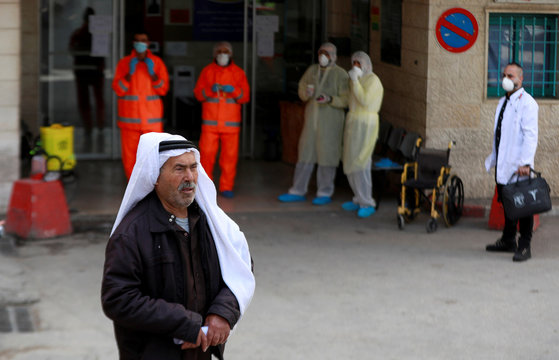 A Palestinian man stands outside a hospital as members of a medical team wear masks amid coronavirus precautions, in Beit Jala town in the Israeli-occupied West Bank